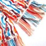 Snow Fleece Scarf: These luxurious scarves wrap around once, twice and are fashioned with a frisky fringe.The design motives are painted and collaged one-at-a-time, creating playful variations on a musical theme. Made with the softest off-white polyester fleece. Machine wash. Size: 7.5 in. wide, 68 in. long